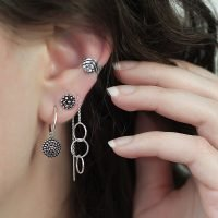 Pair of silver J-hoop earrings with a Jawan ornamental coin charm. - Ozz Silver Jewelry
