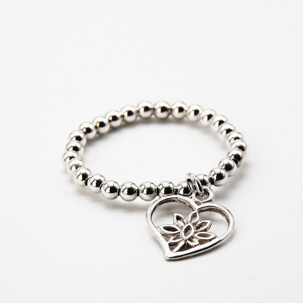 """Handcrafted Bali style ring with real silver beads and flower heart charm. Flexible elastic thread, roughly 18mm. <a href=""""https://www.ozz-jewelry.com/size-guides/"""" target=""""_blank"""" rel=""""noopener noreferrer"""">See size guide</a>. - Ozz Silver Jewelry"""