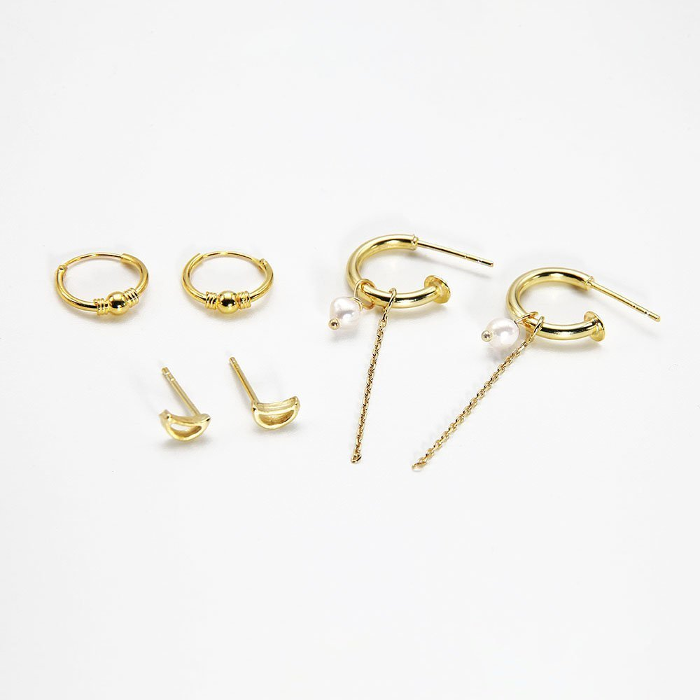 <strong>Web Exclusive:</strong> This pack includes 3 pairs of 18K gold plated silver earrings: dainty moon outline earrings, 12mm Bali hoop earrings, and J-hoops with an authentic pearl and hanging chain detail. Together, they make for an ultra-feminine collection in gold, beautiful individually and combined. - Ozz Silver Jewelry