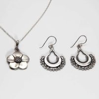 <strong>Web Exclusive:</strong> This pack includes a sterling silver flower pendant necklace, alongside a pair of sterling silver Bali hook earrings. Both the necklace and the earrings are decorated with Jawan, a decorative art originating in Bali, which uses small droplets of silver to create a pattern. - Ozz Silver Jewelry