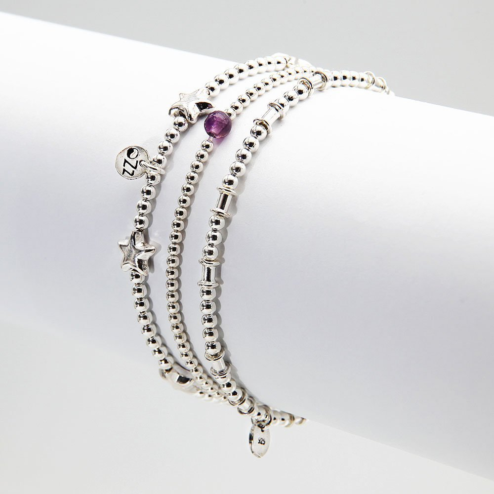 A pack of 3 sterling silver Bali bracelets. Each bracelet is hand-threaded on an elastic silicone thread and contains an OZZ authentic charm. The Black Heart Pack includes an Amethyst gemstone bracelet with sterling silver beads. - Ozz Silver Jewelry