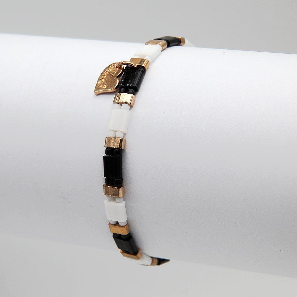 This bracelet is threaded on an elastic band. It features monochromatic beads with stainless steel touches in a gold finish. - Ozz Silver Jewelry