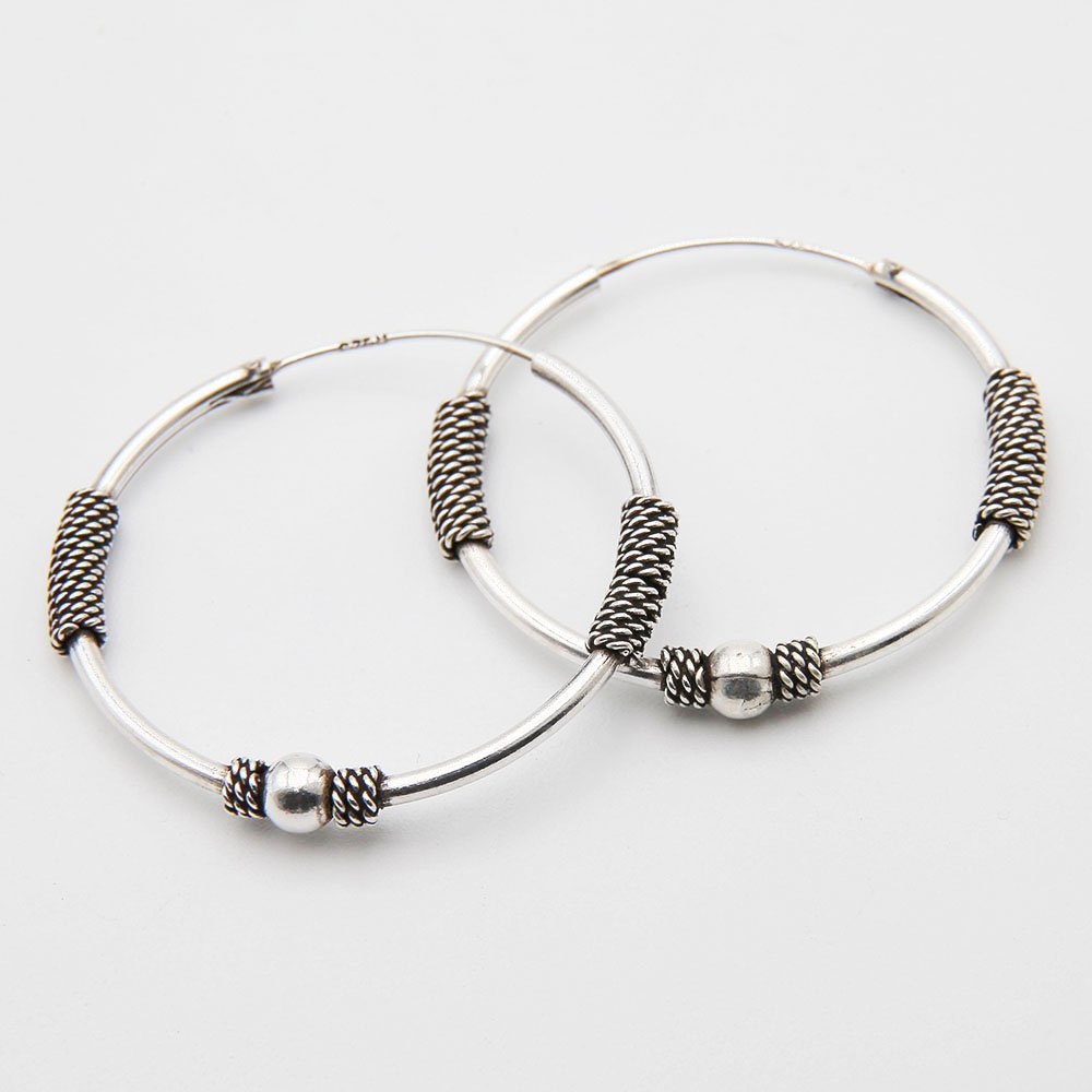 A pair of 30mm silver Bali hoop earrings, featuring a decorative woven basket design and silver bead. - Ozz Silver Jewelry