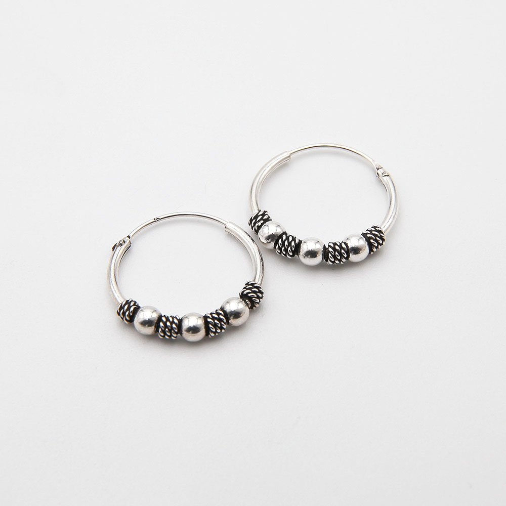 A pair of silver Bali hoop earrings, featuring a decorative woven basket design and silver beads. - Ozz Silver Jewelry